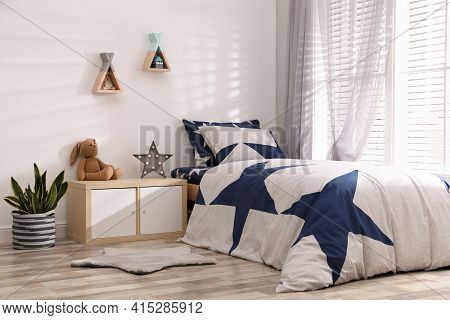 Bed With Stylish Linens In Children's Room