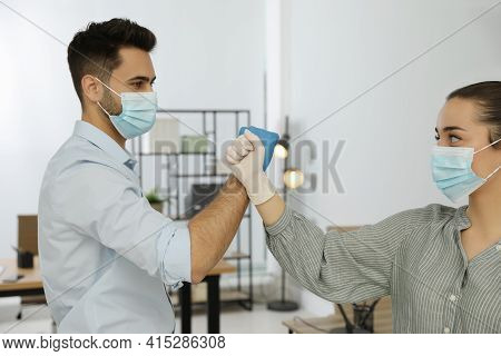 People Greeting Each Other By Bumping Fists Instead Of Handshake In Office