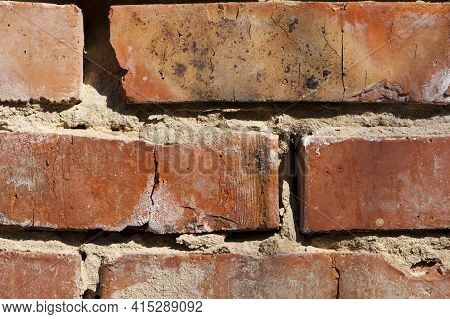 Old Brick Wall. Decorative Wall Made Of Destroyed Dark Red Bricks. Background For Design On A Constr