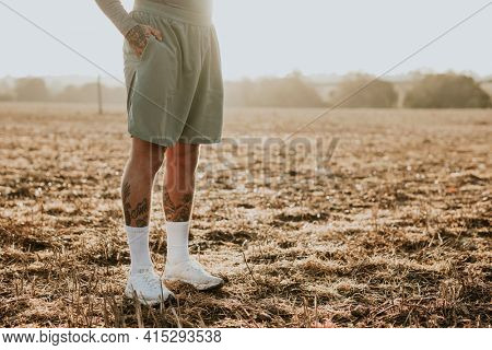 Tattooed man in running shorts standing in countryside at sunset