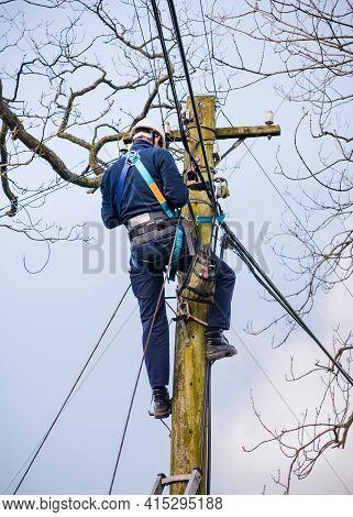 Conwy, Uk - February 29, 2012. Bt Openreach Telecoms Engineer Repairing An Overhead Phone Line. Tech