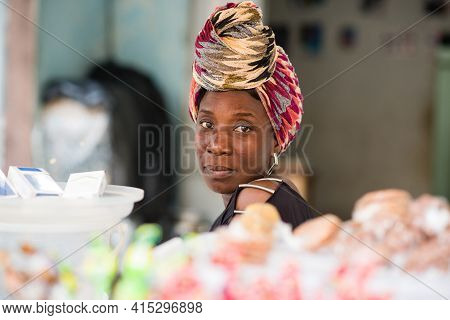 Mature Saleswoman Sitting Behind Her Candy Stand Looking At The Camera.