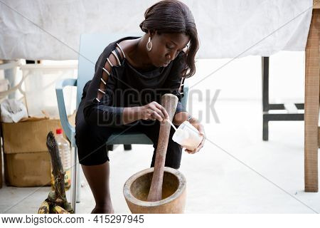 African Saleswoman Sitting At The Market Behind Her Display And Pounding The Dried Spices