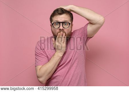 Shocked, Strange Man With Glasses In Fright Covers Mouth With One Hand, Put The Other On Head And Lo