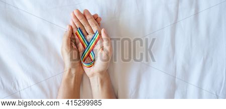 Hand Showing Lgbtq Rainbow Ribbon On White Bed Background. Support Lesbian, Gay, Bisexual, Transgend