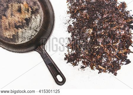 Old Skillet. A Pile Of Rusty, Dirty Soot From The Bottom Of The Pan On A White Background.