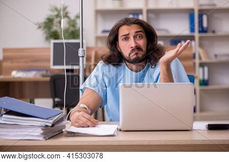 Young sick male employee in blood transfusion concept