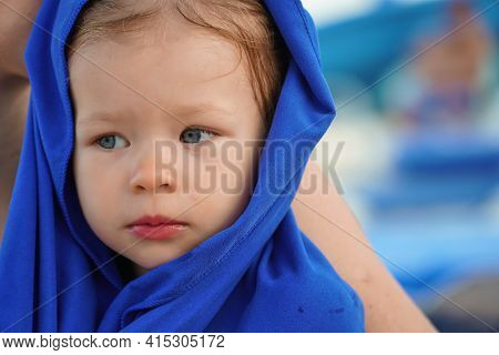 Infant In A Blue Hood Looks Sideways. A Serious And Sad Child Wants To Sleep. Sleepy Baby In A Blue
