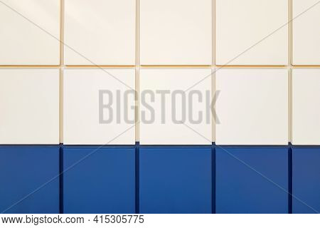 Close-up Wall Tiles In Beige And Dark Blue Laid Out In A Neat Even Row On The Facade Of The Building