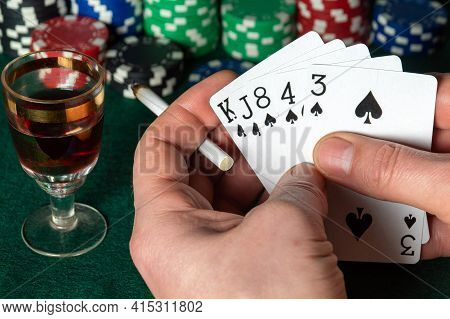 Poker Cards With Flush Combination. Close Up Of Gambler Hand Is Holding Playing Cards In Poker Club