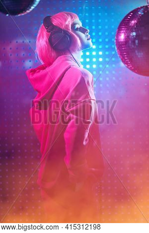 Disco girl with bright glitter make-up and pink hair poses with disco ball and headphones in smoky nightclub in neon light. Night party. DJ girl.