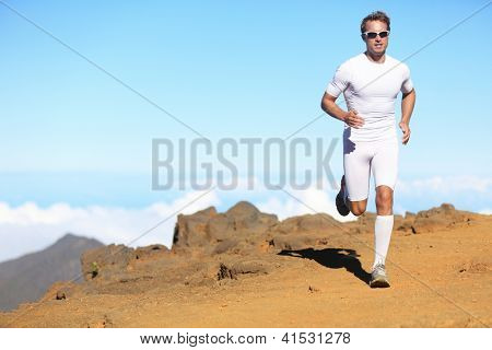 Runner man trail running in scenic landscape nature in compression clothing. Young fit male fitness athlete training outdoor for marathon.