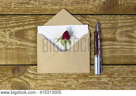 Simple Small Envelope With Space For Writing And Cute Small Rose On Wooden Background With A Pen Clo