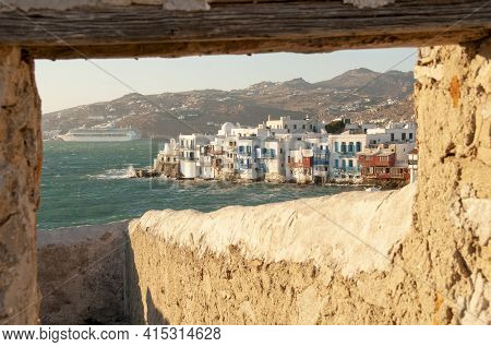 Waterfront Promenade Of Mykonos Village In Greece Through A Natural Stone Window. In The Background