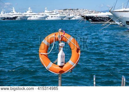 Lifebuoy Orange On Vertical Iron, Sea, Boats, Town Background.