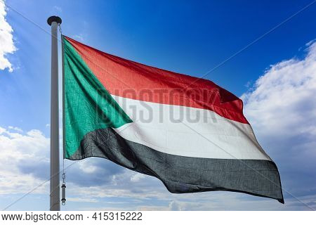 Sudan Flag, Republic Of Sudan National Symbol On A Flagpole Waving Against Blue Cloudy Sky