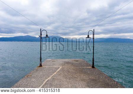 Oropos Sea Gulf Of Evia, Greece Background. Lanterns On Pier.