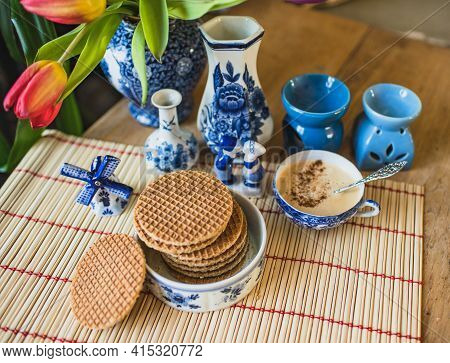 Typical Dutch Blue Crockery On The Table With Traditional Dutch Cookies Stroopwafels And Fresh Red T