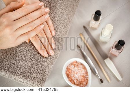 Woman fingers with beautiful nails on brown towel with manicure tools. Close up of woman hands on a towel after manicure. Top view of beautiful natural manicured woman hands.
