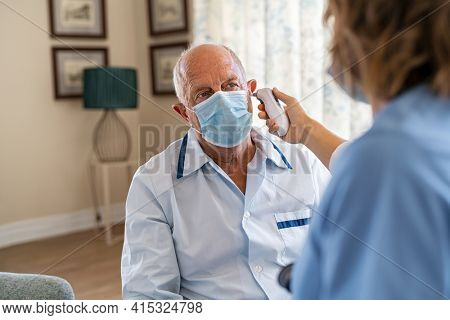 Senior man wearing face mask for safety against covid-19 and getting ear temperature checked by nurse at home. Nurse checking ear temperature of old patient using electronic tympanic thermometer.