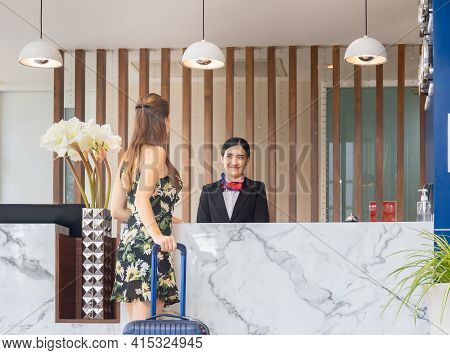 Rear View Of Guest Standing At Hotel Counter With Blurred Female Receptionist, Young Travellers Stan