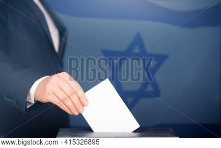 Election in Israel. Hand of voter putting vote in the ballot box. Waved Israel flag on background.