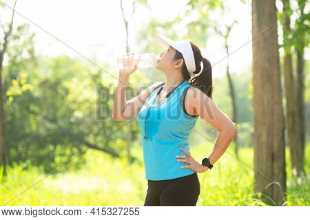 Healthy Athletic Woman Drinking Pure Water After Go Running To Be Fresh In The Nature Park. Asian Ru
