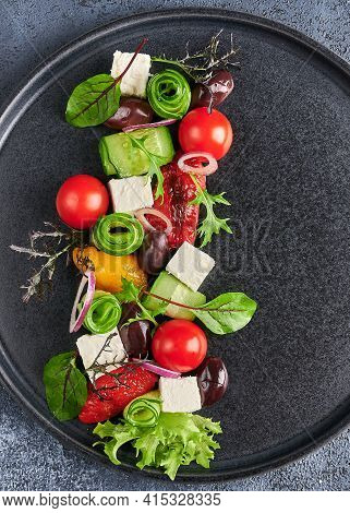 Fresh Greek Salad With Tomato, Cucumber, Bel Pepper , Olives And Feta Cheese On Dark Textured Plate,