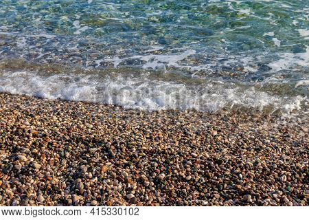 Sea Tide On Pebble Shore Of The Mediterranean Sea. Waves With White Foam On Pebble Beach