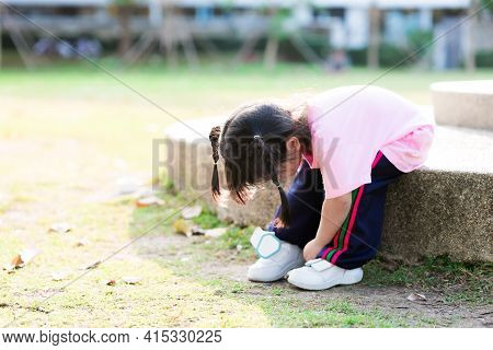Cute Girl Is Trying To Wear Tight Shoes On Her Own. Child Wear White Sneakers. Children Get Ready To