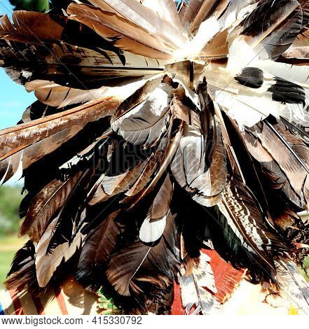 Colorful Native American Bonnet Feathers Headdress Displayed Outdoors.