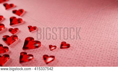 Valentine's Day, Anniversary Concept Background. Translucent Shiny Red Hearts On Pink Wool Surface.
