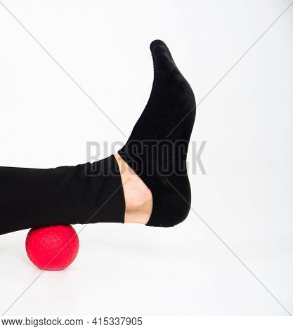 Massager Red Ball For Legs And Calves. Close-up Of A Girls Legs In Black Leggings On A White Backgro