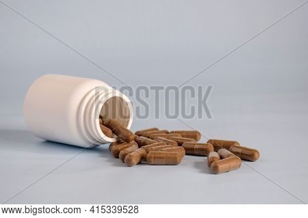 Natural Brown Capsules With Pressed Medicinal Herb,pills In Open Upturned Plastic Jar On Table Front