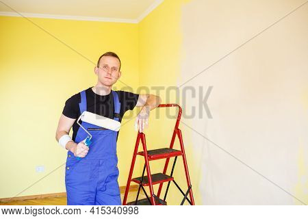 Handsome Man In Overalls Hold Paint Roller,. Tools Accessories For Apartment Room Renovation. Home R