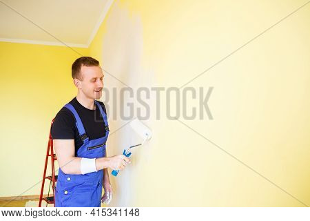 Young Man In Overalls Hold A Paint Roller. Tools Accessories For Apartment Room Renovation. Home Ren