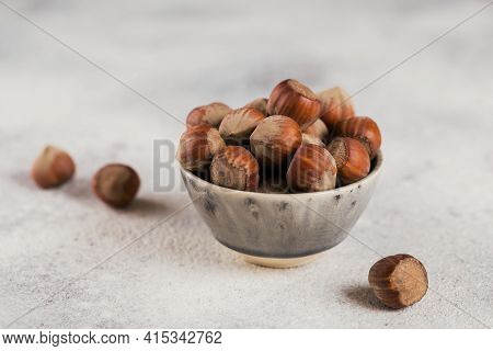 Pile Of Hazelnuts Filbert In A Bowl On A White Background. Fresh Nuts In Their Shells.