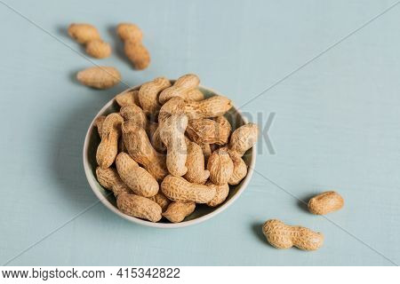 Pile Of Peanuts In A Bowl On A Light Blue Background. Fresh Nuts In Their Shells.