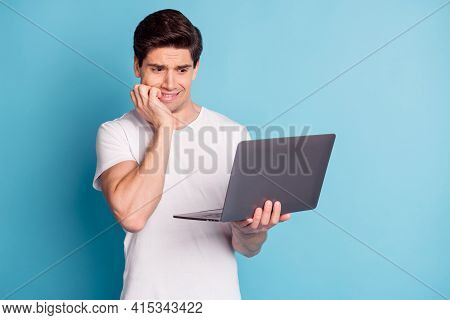 Photo Of Sad Nervous Guy Hold Laptop Wear White T-shirt Bite Hand Isolated On Cyan Color Background