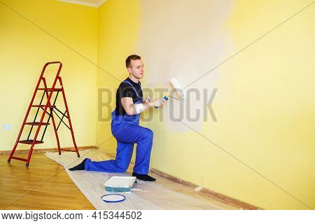 A Man Paints The Wall In The House With A Roller And Paint. Renovation Of Rooms In The House.