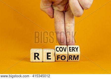 Recovery And Reform Symbol. Businessman Turns Cubes And Changes The Word 'recovery' To 'reform'. Bea