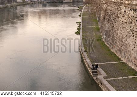 Rome. Italy. Spring 2020. Spring Roman Embankments. Couples Sit On The Steps Of The Tiber Embankment