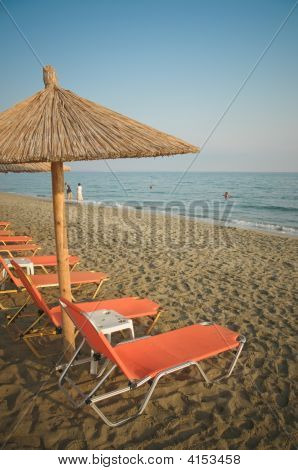 Deck chairs and beach umbrellas on a beach in Nei Pori Greece poster