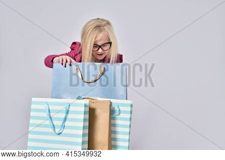 Teenage Girl Looks With Curiosity In Paper Bags From The Store.