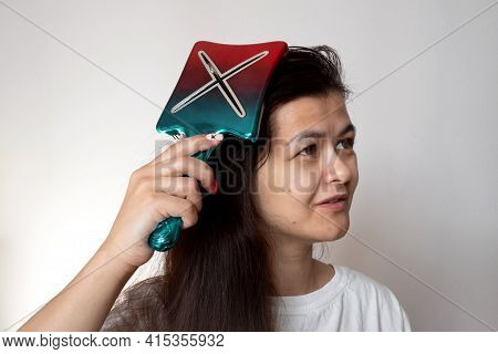 Woman Combing Her Long Black Hair With Big Colored Comb. Long Hair Daily Routine.