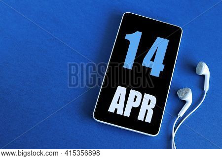 April 14. 14 St Day Of The Month, Calendar Date. Smartphone And White Headphones On A Blue Backgroun