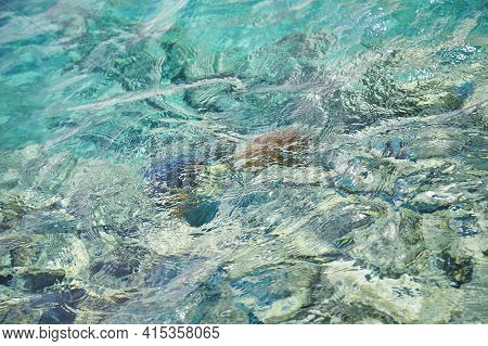 Crystal Turquoise Water Of The Red Sea. Background Of The Red Sea Water Surface. Top Down View Of Th