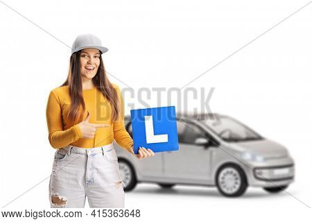 Young female driver with a learner plate and a small silver car isolated on white background