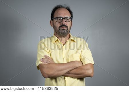 Person Dressed In Yellow Shirt With Crossed Arms In Neutral Background