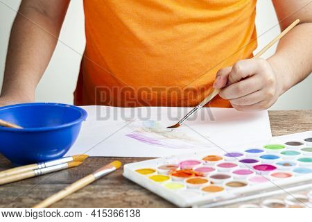 A Caucasian Boy Is Drawing An Abstract Picture On A White Paper Using A Set Of Watercolor. He Is Lef